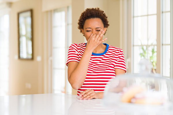woman holding nose in kitchen