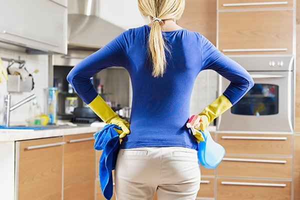 woman wearing cleaning gloves holding household cleaner